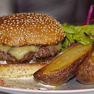 Burger Steack haché, Curé Nantais, tomate fraîche, oignons rouge bacon, cornichon, sauce burger avec ses grenailles rôties