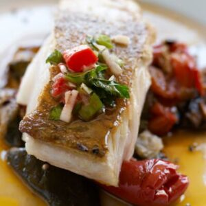 Aiglefin rôti aux échalotes, croûte de parmesan,  sauce homardine, pousses d'épinard et caviar aubergine.
